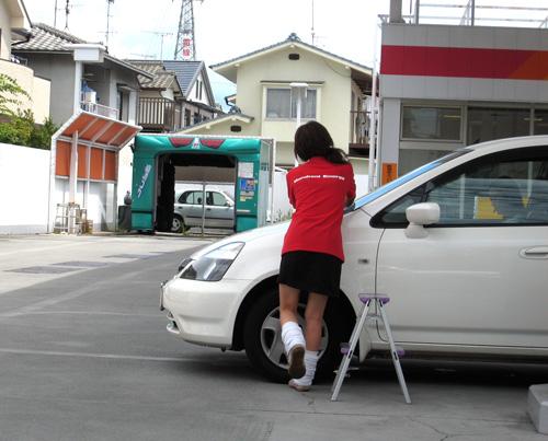 ガソリンスタンドで車の窓をふく店員